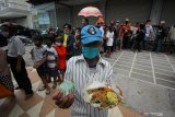 Warga memperlihatkan menu makan gratis yang didapatkan dari gerobak makanan milik Setiyono di jalan Kedungsari, Surabaya, Jawa Timur, Selasa (27/10/2020). Aksi sosial pemberian makan gratis untuk semua orang sebanyak 100 porsi setiap hari tersebut guna membantu meringankan beban ekonomi masyarakat di tengah pandemi COVID-19. Antara Jatim/Moch Asim/zk.