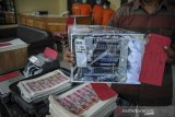 Petugas kepolisian berpakaian sipil menunjukan barang bukti berupa foto mesin produksi uang palsu pecahan seratus ribu rupiah saat rilis kepada awak media di Polrestabes Bandung, Jawa Barat, Rabu (28/10/2020). Polrestabes Bandung berhasil menangkap empat orang tersangka yang telah memproduksi uang palsu pecahan seratus ribu rupiah senilai Rp 800 juta yang diancam dengan hukuman pidana paling lama 15 tahun kurungan penjara. ANTARA JABAR/Raisan Al Farisi/agr