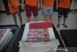 Tersangka dan barang bukti berupa uang palsu pecahan seratus ribu rupiah di hadirkan kepada awak media saat rilis di Polrestabes Bandung, Jawa Barat, Rabu (28/10/2020). Polrestabes Bandung berhasil menangkap empat orang tersangka yang telah memproduksi uang palsu pecahan seratus ribu rupiah senilai Rp 800 juta yang diancam dengan hukuman pidana paling lama 15 tahun kurungan penjara. ANTARA JABAR/Raisan Al Farisi/agr