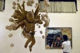 Pengunjung mengamati karya seni rupa yang dipajang dalam pameran bertajuk Bali Megarupa 'Candika Jiwa: Melampaui Medium, Ruang dan Waktu' di kawasan Ubud, Gianyar, Bali, Rabu (28/10/2020). Pameran rangkaian Festival Seni Bali Jani II yang diselenggarakan Pemprov Bali tersebut menampilkan puluhan karya seni berbagai jenis seperti lukisan, patung dan instalasi karya 45 orang seniman. ANTARA FOTO/Fikri Yusuf/nym.