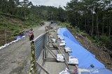Kendaraan roda dua melintas di samping lokasi longsor, Desa Najaten, Cibalong, Kabupaten Garut, Jawa Barat, Jumat (30/10/2020). Sebagian badan jalan lintas selatan penghubung Garut-Tasikmalaya yang longsor tersebut sudah bisa dilalui kendaraan roda dua maupun roda empat yang akan berwisata menuju pantai selatan. ANTARA JABAR/Candra Yanuarsyah/agr.