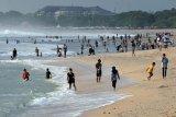 Wisatawan berlibur pada liburan panjang Hari Maulid Nabi Muhammad SAW di Pantai Kuta, Badung, Bali, Jumat (30/10/2020). Obyek wisata terpopuler di Bali tersebut kembali ramai dikunjungi wisatawan yang sebagian besar turis domestik setelah sempat sepi kunjungan akibat terdampak pandemi COVID-19. ANTARA FOTO/Nyoman Hendra Wibowo/nym.