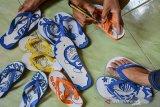 Perajin  Lufi Iskandar menyelesaikan pembuatan sandal jepit karakter di Gunung Ceuri, Kota Tasikmalaya, Jawa Barat, Sabtu (31/10/2020). Lufi yang biasa sehari-hari bekerja di bengkel las ketok beralih profesi menjadi perajin sandal karakter akibat sepi orderan di saat pandemi COVID-19 dan sandal jepit karakter yang dijual dengan harga Rp25.000 per buah dipasarkan melalui platfrom digital guna bisa bertahan hidup. ANTARA JABAR/Adeng Bustomi/agr