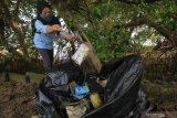 Warga memunguti sampah plastik yang berserakan di pantai di kawasan Greges, Surabaya, Jawa Timur, Sabtu (31/10/2020). Kegiatan bersih-bersih sampah plastik serta menanam bibit tanaman Mangrove yang dilakukan Jaga Segara bersama sejumlah mahasiswa dan warga setempat tersebut wujud kepedulian terhadap lingkungan di kawasan pantai. Antara Jatim/Didik/Zk