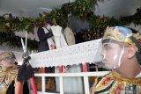 Tokoh adat membuka kain penutup Gong Kiai Pradah saat tradisi jamasan di Bale Alun-Alung Lodoyo Blitar, Jawa Timur, Sabtu (31/10/2020). Tradisi jamasan (mencuci) Gong Kiai Pradah atau Kiai Bicak yang oleh Kementerian Pendidikan dan Kebudayaan RI (Kemendikbud) ditetapkan sebagai Warisan Budaya Tak Benda (WBTB)  sejak tahun 2017 tersebut rutin dilaksanakan pada bulan mulud (Rabi'ul Awal) penanggalan jawa. Antara Jatim/Irfan Anshori/zk.