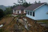 Penjaga sekolah melihat kondisi tanah longsor di sekitar gedung sekolah di SMAN 3 Cibeber, Lebak, Banten, Minggu (1/11/2020). Menurut keterangan pihak sekolah SMAN 3 Cibeber, curah hujan tinggi yang terjadi sejak Jumat (30/10) menyebabkan dua ruang kelas, ruang perpustakaan dan musala terancam amblas karena tanah longsor dan hingga kini kondisi tanah longsor tersebut terus bergerak. ANTARA FOTO/Muhammad Bagus Khoirunas/agr/aww.