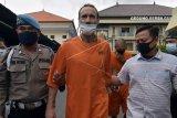 Polisi menggiring warga negara Australia Travis James McLeod (tengah) saat konferensi pers kasus narkotika di Polresta Denpasar, Bali, Rabu (11/11/2020). Polisi menangkap warga negara Australia tersebut di kediamannya di Kerobokan Kelod, Kuta Utara dengan barang bukti berupa 0,86 gram sabu-sabu dan olahan daun kratom yang diduga efeknya sejenis dengan narkotika. ANTARA FOTO/Nyoman Hendra Wibowo/nym.