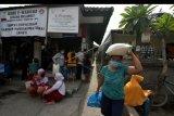 Warga dari Keluarga Penerima Manfaat (KPM) membawa sembako saat pencairan bahan pangan pokok secara non tunai menggunakan Kartu Keluarga Sejahtera (KKS) di Kube E-Warong Sedana Melangit, Kelurahan Panjer, Denpasar, Bali, Minggu (15/11/2020). Kube (Kelompok Usaha Bersama) E-Warong tersebut menyediakan bahan pokok dengan harga murah untuk melayani 197 KPM dari tiga kelurahan/desa di Denpasar. ANTARA FOTO/Nyoman Hendra Wibowo/nym.