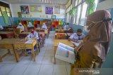 Simulasi Belajar Tatap Muka Di Kota Banjarmasin. Sejumlah siswa mengikuti simulasi belajar tatap muka di SMP Negeri 7 Banjarmasin, Kalimantan Selatan, Senin (16/11/2020). Berdasarkan surat pernyataan orang tua dan persetujuan guru, Pemerintah Kota Banjarmasin melakukan simulasi belajar tatap muka pertama sejak pandemi COVID-19, selama dua minggu di empat sekolah menengah pertama (SMP) di mana lokasi sekolah berada di zona hijau berdasarkan penilaian Gugus Tugas dengan jumlah siswa terbatas serta wajib mematuhi protokol Kesehatan COVID-19.Foto Antaranews Kalsel/Bayu Pratama S.