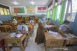 Simulasi Belajar Tatap Muka Di Kota Banjarmasin. Seorang guru memberikan soal kepada siswa saat simulasi belajar tatap muka di SMP Negeri 7 Banjarmasin, Kalimantan Selatan, Senin (16/11/2020). Berdasarkan surat pernyataan orang tua dan persetujuan guru, Pemerintah Kota Banjarmasin melakukan simulasi belajar tatap muka pertama sejak pandemi COVID-19, selama dua minggu di empat sekolah menengah pertama (SMP) di mana lokasi sekolah berada di zona hijau berdasarkan penilaian Gugus Tugas dengan jumlah siswa terbatas serta wajib mematuhi protokol Kesehatan COVID-19.Foto Antaranews Kalsel/Bayu Pratama S.