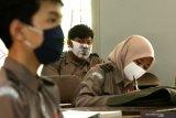 Siswa menggunakan masker pada uji coba sekolah tatap muka di SMA Taruna Bangsa Banyuwangi, Jawa Timur, Senin (16/11/2020). Sebanyak 57 SMA/SMK Sederajat di Banyuwangi melakukan uji coba pembelajaran tatap muka yang pada satu minggu pertama diprioritaskan untuk siswa kelas X karena semenjak masuk SMA mereka belum pernah duduk di bangku sekolah akibat pandemi COVID-19. Antara Jatim/Budi Candra Setya/zk