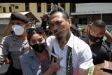 Petugas menggiring penabuh drum grup musik Superman is Dead (SID) I Gede Ary Astina alias Jerinx (kedua kanan) yang didampingi istrinya Nora Alexandra (kedua kiri) usai menjalani sidang putusan di Pengadilan Negeri Denpasar, Bali, Kamis (19/11/2020). Majelis Hakim menjatuhkan vonis hukuman satu tahun dua bulan penjara dan denda 10 juta rupiah subsider satu bulan kurungan terhadap Jerinx karena dinilai bersalah dalam kasus ujaran kebencian dan pencemaran nama baik yang dilaporkan Ikatan Dokter Indonesia (IDI) Bali. ANTARA FOTO/Nyoman Hendra Wibowo/nym.