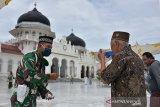 Anggota TNI membagikan masker kepada jamaah sebelum berlangsung shalat Jumat di Masjid Raya Baiturrahman, Banda Aceh, Aceh, Jumat (20/11/2020). Hasil rapat koordinasi ulama dan umara di Aceh menyepakati masjid sebagai pusat edukasi dalam pencegahan dan penyebaran COVID-19 serta meminta para dai, khatib dan imam masjid/meunasah dalam berbagai kesempatan memberikan nasehat dan bimbingan kepada warga menerapkan protokol kesehatan.  Antara Aceh/Ampelsa.