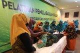 Peserta membalut relawan dengan kain kafan saat pelatihan pemulasaraan jenazah yang diselenggarakan pemerintah daerah Kota Kediri di Kota Kediri, Jawa Timur, Jumat (20/11/2020). Pelatihan yang diikuti oleh perwakilan Gabungan Organisasi Wanita (GOW) tersebut bertujuan memberikan keterampilan pemulasaraan jenazah sesuai dengan syariat Islam dan protokol kesehatan COVID-19. Antara Jatim/Prasetia Fauzani/mas.