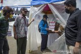 Saksi Pasangan Calon Kepala daerah menyaksikan warga saat mengikuti simulasi pemungutan suara Pilkada Kabupaten Bandung 2020 dengan menggunakan bilik khusus di TPS 109, Baleendah, Kabupaten Bandung, Jawa Barat, Sabtu (21/11/2020). Komisi Pemilihan Umum RI menyediakan bilik khusus pemungutan suara bagi pemilih yang memiliki suhu tubuh tinggi atau gejala sakit untuk mencegah resiko penularan COVID-19 pada Pilkada Serentak 2020 desember mendatang. ANTARA JABAR/Novrian Arbi/agr