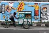 Pengendara melintas di depan mural Pemilu 2020 di kawasan Candi, Sidoarjo, Jawa Timur, Selasa (24/11/2020). Mural tersebut sebagai salah satu bentuk sosialisasi serta menarik keikutsertaan masyarakat untuk menggunakan hak suaranya dalam Pemilu pada 9 Desember mendatang. Antara Jatim/Umarul Faruq/um
