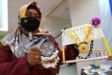 Seorang perajin dari kelompok UMKM Salvador Dali menunjukan produk kerajinan tangan kalung pada pameran UMKM di Kantor Perwakilan Bank Indonesia (BI) Provinsi Gorontalo di Kota Gorontalo, Gorontalo, Senin (23/11/2020). UMKM tersebut membuat berbagai produk dengan memanfaatkan sisik ikan karang menjadi bros, kalung dan hiasan meja yang dijual dengan harga mulai dari Rp20 ribu hingga Rp60 ribu per buah. ANTARA FOTO/Adiwinata Solihin/foc.