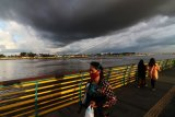 Awan hitam menyelimuti sebagian langit di tepian Sungai Kapuas di Pontianak, Kalimantan Barat, Jumat (20/11/2020). Badan Meteorologi, Klimatologi dan Geofisika (BMKG) menyatakan fenomena La Nina turut terjadi di sebagian wilayah Kalimantan Barat pada November 2020 hingga Januari 2021, dan hal tersebut memicu peningkatan curah hujan yang berpotensi menimbulkan banjir, angin puting beliung serta tanah longsor. ANTARA FOTO/Jessica Helena Wuysang/wsj.