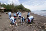 Petugas membersihkan sampah di Pantai Cemara, Banyuwangi, Jawa Timur, Rabu (25/11/2020). Pengelola pantai mengatakan gelombang tinggi yang terjadi sejak (5/11) itu mengakibatkan penumpukan sampah di pantai dan sekitar seribu pohon Cemara tumbang. Antara Jatim/Budi Candra Setya/Um