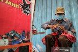Untung, menjahit sepatu dengan tetap mematuhi protokol kesehatan di Jalan Buya Hamka Kabupaten Jombang, Jawa Timur, Kamis (26/11/2020). Dalam sehari ia bisa menjahit 2-3 sepatu dengan upah Rp10 ribu per sepasang, serta rata-rata menjual 5 pasang sandal dengan harga mulai Rp35 ribu-Rp100 ribu. Antara Jatim/Syaiful Arif/Um