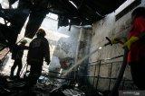 Petugas melakukan pembasahan area gudang suku cadang kendaraan yang terbakar di Tulungagung, Jawa Timur, Kamis (26/11/2020). Gudang suku cadang kendaraan bermotor di pusat Kota Tulungagung itu terbakar diduga akibat konsleting listrik pemanas air. Antara Jatim/Destyan Sujarwoko/Um