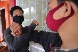 Dua warga melakukan salam siku di Kabupaten Jombang, Jawa Timur, Jumat (27/11/2020). Salam siku sebagai pengganti jabat tangan untuk pencegahan virus Corona. Antara Jatim/Syaiful Arif/Um