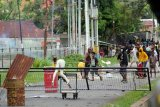 Massa melempari anggota kepolisian saat aksi unjuk rasa di Kota Sorong, Papua Barat, Jumat (27/11/2020). Demonstrasi yang belum diketahui maksud dan tujuannnya tersebut dibubarkan kepolisian karena menyebabkan keramaian di tengah pandemi COVID-19 dan berlangsung ricuh sehingga mengakibatkan empat orang anggota polisi dan satu orang jurnalis terluka. ANTARA FOTO/Olha Mulalinda/nym.