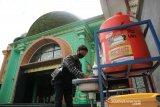 Warga mencuci tangan sebelum shalat di Masjid Jami Al Fattah Kota Mojokerto, Jawa Timur, Sabtu (28/11/2020). Takmir masjid menerapkan protokol kesehatan ketat dengan melakukan sterilisasi jamaah, wajib masker, cuci tangan dan shaf berjarak minimal 30 cm ketika melaksanakan shalat untuk mencegah penyebaran COVID-19. Antara Jatim/Syaiful Arif/mas.