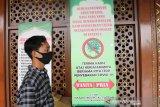 Jamaah melintas di depan himbauan wajib memakai masker saat shalat di Masjid Jami Al Fattah Kota Mojokerto, Jawa Timur, Sabtu (28/11/2020). Takmir masjid menerapkan protokol kesehatan ketat dengan melakukan sterilisasi jamaah, wajib masker, cuci tangan dan shaf berjarak minimal 30 cm ketika melaksanakan shalat untuk mencegah penyebaran COVID-19. Antara Jatim/Syaiful Arif/mas.