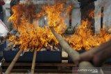 Petugas memusnahkan barang bukti tindak pidana di halaman gedung Kejaksaan Negeri Kota Bandung, Jawa Barat, Selasa (1/12/2020). Kejaksaan Negeri Kota Bandung memusnahkan barang bukti perkara tindak pidana berupa narkotika, alat perjudian, senjata api, dan senjata tajam hasil kejahatan periode Mei 2020 hingga Oktober 2020. ANTARA JABAR/Raisan Al Farisi/agr