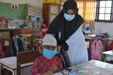 Guru membantu memakaikan masker kepada murid di salah satu Sekolah Dasar Negeri, Desa Garut, Kecamatan Darul Imara, Kabupaten Aceh Besar, Aceh, Selasa (2/12/2020). Pemerintah Aceh meluncurkan Gerakan Masker Sekolah (Gemas) dalam mencegah penyebaran COVID-19 dengan menyasar sebanyak 1,08 juta pelajar dari 6.783 sekolah di Aceh, namun masker yang dibagikan kepada murid sekolah dasar itu ukuran dewasa dan tidak sesuai dengan ukuran anak sekolah dasar, sehingga tidak dapat dimanfaatkan. Antara Aceh/Ampelsa.