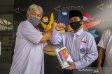 Kepala LKBN ANTARA Biro Kalimantan Selatan Nurul Aulia Badar (kiri) menyerahkan bantuan gawai kepada siswa berprestasi Akhmad Bukhari (kanan) di Kantor LKBN ANTARA Biro Kalsel di Banjarmasin, Kalimantan Selatan, Kamis (3/12/2020). Dalam rangkaian HUT Ke-83 Perum LKBN ANTARA memberikan bantuan gawai guna menunjang pendidikan anak  pekerja pers berprestasi di Provinsi Kalimantan Selatan. Foto Antaranews Kalsel/Bayu Pratama S.