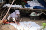 Perajin menyelesaikan proses pembuatan batik tulis, di Desa Klampar,  Pamekasan, Jawa Timur, Jumat (4/12/2020). Dalam sebulan terakhir produksi batik di daerah itu naik sekitar 25 persen atau naik dari 200 potong menjadi 250 potong hasil tiap perajin per pekan, karena meningkatnya permintaan dari sejumlah daerah. Antara Jatim/Saiful Bahri/mas.