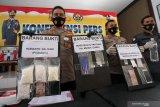Kapolres Blitar Kota AKBP Leonard M. Sinambela (Kiri) menunjukkan alat bukti ribuan butir obat-obatan berbahaya yang berhasil diamankan saat rilis di Mapolres Blitar Kota, Jawa Timur, Jumat (4/12/2020). Operasi cipta kondisi tersebut bertujuan untuk menjaga situasi kamtibmas di wilayah itu, terutama jelang H-5 hingga hari H pelaksanaan Pilkada Serentak 2020. Antara Jatim/Irfan Anshori/mas.
