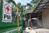 Petugas Palang Merah Indonesia (PMI) menyemprotkan cairan disinfektan di lingkungan sekitar rumah warga yang meninggal akibat positif COVID-19 di Kota Madiun, Jawa Timur, Sabtu (5/12/2020). Penyemprotan tersebut dimaksudkan untuk pencegahan penularan COVID-19 di Kota Madiun. Antara Jatim/Siswowidodo/Um