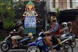Pengendara motor melaju di dekat alat peraga sosialisasi (APS) Pemilihan Wali Kota (Pilwali) 2020 yang diikutkan pada lomba di Denpasar, Bali, Minggu (6/12/2020). Lomba pembuatan dan pemasangan APS yang digelar oleh KPU Kota Denpasar tersebut untuk mengajak masyarakat datang ke TPS dan menggunakan hak pilih dalam Pilkada serentak pada 9 Desember 2020. ANTARA FOTO/Nyoman Hendra Wibowo/nym.