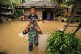 Anggota Babinsa TNI Kodim 0103 Aceh Utara membantu evakuasi korban banjir di Desa Hasan Kareung, Blang Mangat, Lhokseumawe, Aceh, Sabtu (5/12/2020). Data Badan Penanggulangan Bencana Daerah (BPBD) menyebutkan bencana banjir terus meluas, merendam 502 desa di 20 kecamatan di Aceh Utara, menyebabkan sekitar seribu warga mengungsi. ANTARA FOTO/Rahmad/foc.