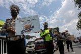 Petugas kepolisian melakukan sosialisasi kepada pengendara yang melintas di jalan Raya Waru, perbatasan Surabaya - Sidoarjo, Jawa Timur, Selasa (8/12/2020). Sosialisasi tersebut untuk mengajak dan mengimbau masyarakat menggunakan hak suaranya dalam Pilkada serentak 2020 dengan tetap menerapkan protokol kesehatan. Antara Jatim/Umarul Faruq/Um