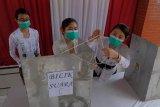 Petugas KPPS menyiapkan bilik suara di TPS 17, Banjar Kertasari, Kelurahan Panjer, Denpasar, Bali, Rabu (9/12/2020). Petugas KPPS di TPS yang semuanya diisi oleh perempuan itu sebagai simbol perempuan Bali mampu berpartisipasi dalam Pilkada serentak 2020. ANTARA FOTO/Nyoman Hendra Wibowo/nym.