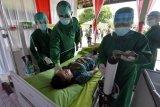 Petugas kesehatan memberikan penanganan lanjutan kepada seorang Aparatur Sipil Negara (ASN) yang mengalami reaksi usai divaksin COVID-19 saat simulasi di lingkungan Kodam IX Udayana, Denpasar, Bali, Kamis (10/12/2020). Simulasi tersebut digelar sebagai persiapan penyuntikan vaksinasi COVID-19 yang rencananya digelar pada Januari 2021. ANTARA FOTO/Nyoman Hendra Wibowo/nym.