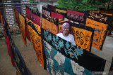 Perajin menjemur batik yang sudah diberi warna di Desa Klampar, Pamekasan, Jawa Timur, Sabtu (12/12/2020). Sejak pertengahan penerapan era normal baru, permintaan batik Pamekasan yang dipasarkan secara daring dan konvensional mulai meningkat sekitar 20 persen atau naik dari 40 potong per pekan menjadi 50 potong. Antara Jatim/Saiful Bahri/mas.