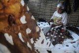 Perajin menyelesaikan pembuatan batik tulis di Desa Klampar, Pamekasan, Jawa Timur, Sabtu (12/12/2020). Sejak pertengahan penerapan era normal baru, permintaan batik Pamekasan yang dipasarkan secara daring dan konvensional mulai meningkat sekitar 20 persen atau naik dari 40 potong per pekan menjadi 50 potong. Antara Jatim/Saiful Bahri/mas.