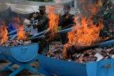 Petugas berwenang membakar rokok ilegal saat pemusnahan barang milik negara di Kantor Pengawasan dan Pelayanan Bea dan Cukai Tipe Madya Pabean A Denpasar, Bali, Selasa (15/12/2020). Dalam kesempatan tersebut, Bea Cukai memusnahkan barang hasil penindakan periode 2019/2020 berupa 2.245 botol minuman mengandung etil alkohol (MMEA), 459.805 batang rokok, 86 bungkus tembakau iris, 297 botol liquid vape, 109 buah alat kesehatan berbagai jenis, 8.873 pakaian, 53 telepon genggam, 944 jam pintar, 46 tablet, 1.337 produk lain berbagai jenis terdiri dari action figure, kartu memori, flashdisk dan aksesoris dengan total jumlah nilai barang yaitu Rp1,997 miliar. ANTARA FOTO/Nyoman Hendra Wibowo/nym