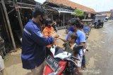 Personel Badan Penanggulangan Bencana Daerah (BPBD) membagikan masker kepada warga di Pasar induk Indramayu, Jawa Barat, Jumat (18/12/2020). Pembagian masker tersebut dalam rangka sosialisasi penerapan protokol kesehatan guna menekan penyebaran COVID-19. ANTARA JABAR/Dedhez Anggara/agr