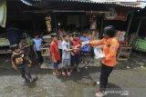 Personel Badan Penanggulangan Bencana Daerah (BPBD) membagikan masker kepada sejumlah anak di Pasar induk Indramayu, Jawa Barat, Jumat (18/12/2020). Pembagian masker tersebut dalam rangka sosialisasi penerapan protokol kesehatan guna menekan penyebaran COVID-19. ANTARA JABAR/Dedhez Anggara/agr