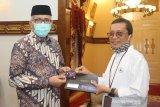 Kacab BNI Syariah Zul Irfan menyerahkan Hasanah Card edisi Qanun Aceh branding Masjid Raya Baiturrahman kepada Gubernur Aceh Nova Iriansyah di Banda Aceh, Sabtu (19/12/2020). Antara Aceh/BNI Syariah/Azhari