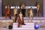 Peragawati memamerkan busana yang dikenakannya saat 'Surabaya Fashion Festival' di Surabaya, Jawa Timur, Minggu (20/12/2020). Berbagai busana karya sejumlah perancang busana dipamerkan dalam peragaan busana tersebut. Antara Jatim/Didik