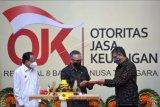 Ketua Dewan Komisioner Otoritas Jasa Keuangan (OJK) Wimboh Santoso (tengah) menyerahkan potongan nasi tumpeng kepada Kepala OJK Regional 8 Giri Tribroto (kanan) disaksikan Gubernur Bali Wayan Koster (kiri) saat peresmian gedung Kantor OJK Regional 8 di Denpasar, Bali, Senin (21/12/2020). Gedung Kantor OJK Regional 8 Bali dan Nusa Tenggara tersebut diharapkan dapat meningkatkan peran dan kontribusi OJK dalam meningkatkan pembangunan di daerah melalui hadirnya sektor keuangan. ANTARA FOTO/Fikri Yusuf/nym.
