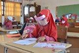 Sejak Maret 2020, aktivitas belajar mengajar sejumlah sekolah berbagai tingkatan pendidikan lumpuh seketika akibat pandemi COVID-19 yang mulai mewabah di Indonesia.     Mulai sekolah PAUD, SD, SMP, SMA serta pesantren hingga perguruan tinggi tutup dan proses belajar mengajar dihentikan guna mencengah penyebaran COVID-19.     Aktivitas belajar mulai diterapkan kembali setelah kasus COVID-19 mereda menurut pembagian zona wilayah yang dinilai aman dari penyebaran COVID-19    Proses belajar mengajar di sekolah harus menerapkan disiplin protokol kesehatan setelah adanya kesepakatan antara orang tua murid dengan pihak sekolah serta arahan dari pemerintah setempat.    Pihak sekolah menyatakan, aktivitas belajar yang kembali dimulai sejak dua bulan terakhir menjelang akhit tahun 2020 itu dibatasi, dalam satu lokal hanya dihadiri 50 persen dari total murid dengan menerapkan protokol kesehatan menggunakan. masker, jagar jarak dan cucu tangan.     Sebelum murid memasuki ruang belajar, pihak sekolah juga melakukan penyemprotan cairan disinfektan untuk sterilisasi bebas dari COVID-19.    Selain pembatasan jumlah murid, pihak sekolah juga mengurangi jam belajar masing masing kelas belajar satu jam dan kemudian diganti dengan murid lainnya dengan waktu belajar yang sama.     Pemberlakukan tersebut tidak hanya diterapkan di sekolah umum, melainkan juga di dayah atau pesantren untuk mencegah penyebaran COVID-19 yang sudah menjadi tanggung jawab semua pihak .    Para orangtua dan murid sekolah berharap kasus COVID-19 segera berlalu, sehingga aktivitas belajar dan mengajar kembali berjalan normal.