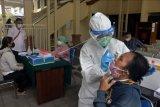 Petugas kesehatan melakukan tes usap terhadap pekerja pariwisata di Pengadilan Negeri Denpasar, Bali, Senin (28/12/2020). Kegiatan tes usap gratis tersebut diikuti sekitar 150 orang dari hakim, pegawai Pengadilan Negeri Denpasar, pengacara, wartawan dan pekerja pariwisata untuk mencegah penyebaran COVID-19. ANTARA FOTO/Nyoman Hendra Wibowo/nym.